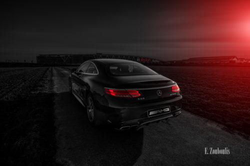 Schwarzweiß Aufnahme einer schwarzen Mercedes Benz AMG S-Klasse Coupè mit roten Elementen. Im Vordergrund der AMG mit roten Heckleuchten und im Hintergrund das Bosch Parkhaus und die Messe am Flughafen Stuttgart. Bild entstanden auf Einladung von Mercedes Benz