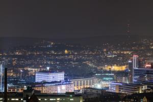 Nächtliches Panorama von Stuttgart. In der Mitte des Bildes befindet sich die Stadtbibliothek und die Innenstadt. Rechts am Bildrand ist der Fernsehturm zu sehen