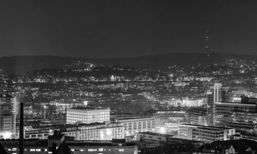 Nächtliches Schwarzweiß Panorama von Stuttgart. In der Mitte des Bildes befindet sich die Stadtbibliothek und die Innenstadt. Rechts am Bildrand ist der Fernsehturm zu sehen