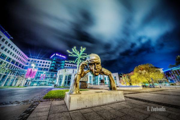 """Nachtaufnahme am Friedrichsbau in Stuttgart. Im Vordergrund die Skulptur """"Denkpartner"""". Im Hintergrund der Friedrichsbau und am Himmel sind am Betrachter vorbeiziehende Wolken in einer bläulichen Abendstimmung"""