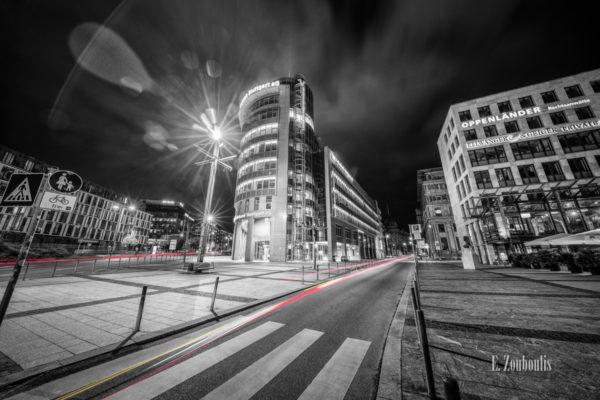 Schwarzweiss Aufnahme am Börsenplatz in Stuttgart bei Nacht. Auf den Straßen sind rote und gelbe Lichtschweife zu sehen, die den Verkehr kennzeichnen.