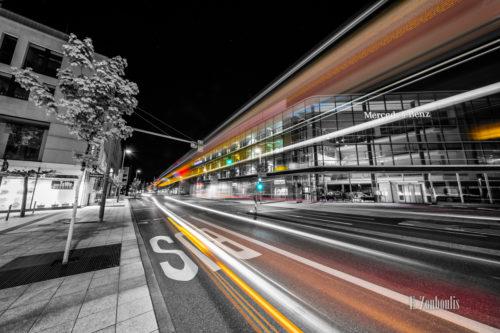 Schwarzweiß Aufnahme bei Nacht in Stuttgart Vaihingen. Der Verkehr ist auf dem Bild durch farbige Lichter und Lichtschweife gekennzeichnet. Im Hintergrund befindet sich das Mercedes Benz Global Training Gebäude