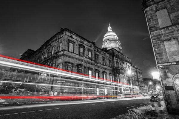 Langzeitaufnahme vor der University of Edinburgh, Schottland mit einem roten Lichtschweif, der den Verkehr nachts vor der Universität sichtbar macht