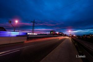 Zur Abenddämmerung in Böblingen. Auf der Brücke der Calwer Straße hinterlassen die vorüber fahrenden Autos rote Lichtschweife. Die Wolken bekommen von der untergehenden Sonne eine rötlich / pinke Farbe