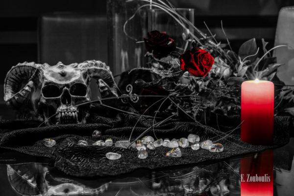 Schwarzweiß Bild mit roten und gelben Elementen. Im Vordergrund Runensteine auf schwarzem Stoff und einer roten Kerze. Im Hintergrund ein Totekopf mit Hörnern von Markus Mayer und rote Rosen
