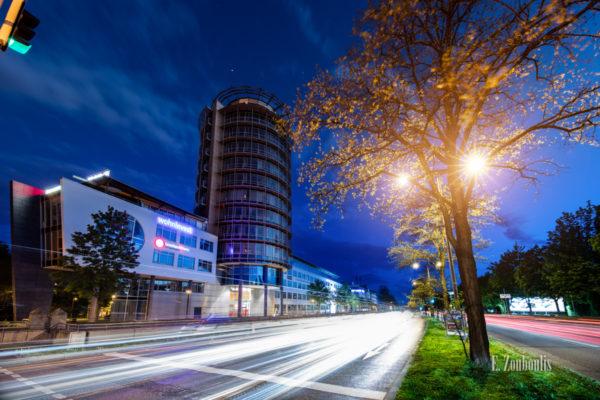 Abendaufnahme zur blauen Stunde am ABB Turm in Stuttgart Degerloch. Im Vordergrund rechts ein Baum und in der Verkehr, der durch die Löffelstraße zieht und einen Lichtschweif hinterlässt