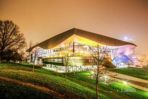 Nachtaufnahme bei Nebel an der BMW Welt in München beim Olympiapark. Im Vordergrund der Rasen, der die letzten Blätter der Bäume auffängt. In der Mitte des Bildes die BMW World mit vielen farbigen Lichtern und im Hintergrund im Nebel das Vierzylinder Gebäude