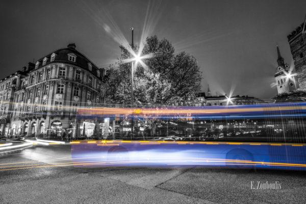 Schwarzweiß Aufnahme bei Nacht in München. Im Vordergrund der farbige Lichtschweif, der einen Bus der Linie 62 erkennen lässt und im Hintergrund die schöne Architektur des alten Gebäude und der Turm der Peterskirche (St. Peter)