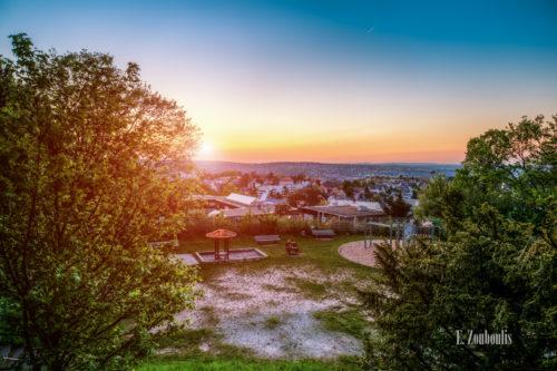 Abendliche Aufnahme zum Sonnenuntergang an der Geroksruhe in Stuttgart mit Blick auf die Innenstadt. Im Vordergrund der Spielplatz und Bäume. Im Hintergrund die Dächer von Stuttgart, die durch die tiefstehende Sonne leuchten