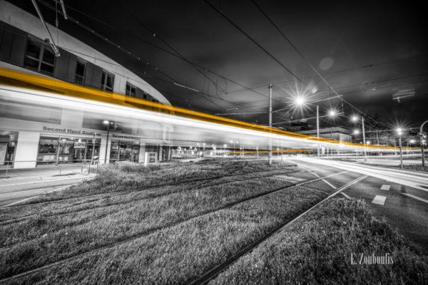 Schwarzweiß Aufnahme bei Nacht am Kelterplatz in Stuttgart Zuffenhausen. Im Vordergrund die Schienen. In der Mitte des Bildes sind die gelben Lichter einer U-Bahn zu erkennen, die quer über die Kreuzung schießt