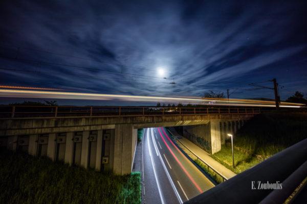 Nachtaufnahme an einer Brücke im Kayertäle in Gärtringen. Im Vordergrund das Geländer einer Fußgängerbrücke und Lichtschweife, die durch den vorbeifahrenden Verkehr entstehen. In der Mitte des Bildes hinterläßt ein Zug sein Restlicht und im Hintergrund werden die vorbeiziehenden Wolken durch den Vollmond erhellt