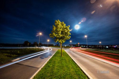 Nachtaufnahme in Gärtringen bei Vollmond. Im Vordergrund ein Baum und die Lichtschweife des Verkehrs, die zum Kreisverkehr hin- und vom Kreisverkehr wegfahren. Im Himmel der Vollmond, der die Wolken erhellt und bläulich schimmern lässt