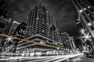Schwarzweiß Aufnahme Nachts in New York City. Der Verkehr ist durch gelbe und rote Lichtschweife gekennzeichnet. Im Vordergrund die West 37th Street mit dem vorbeiziehenden Verkehr. In der Mitte des Bildes eine farbige Ampel und im Hintergrund die Wolken, die über den Spitzen der Hochhäuser zu sehen sind