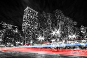 Schwarzweiß Aufnahme nachts in New York City mit einem gelben und blauen Lichtschweif, der den Verkehr kennzeichnet. Im Hintergrund Bäume und die Wolken, die über den Spitzen der Hochhäuser zu sehen sind