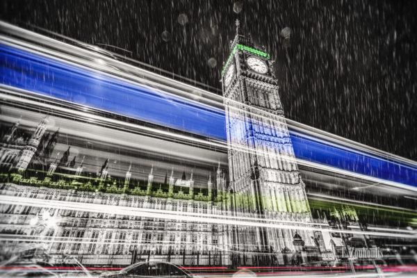 Schwarzweiß Aufnahme bei Nacht vor dem Big Ben in London mit einem farbigen Lichtschweif, der am Palace of Westminster bei strömendem Regen vorbeizieht und den Verkehr sichtbar macht