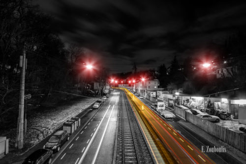 Schwarzweiß Aufnahme bei Nacht in Stuttgart Kaltental. Ein gelber Lichtschweif einer vorbeifahrenden Straßenbahn ist entlang der Schienen zu sehen. Der Frost hat sich auf der Straße abgesetzt. Roter Farbeffekt, die die Straßenbeleuchtung kennzeichnen