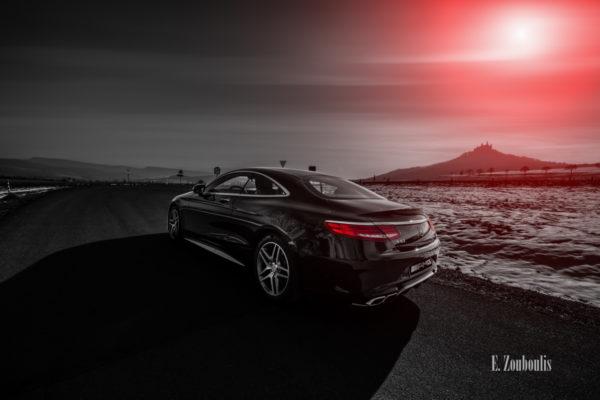 Schwarzweiß Aufnahme mit roten Elementen eines schwarzen Mercedes AMG S63 vor der Burg Hohenzollern. Im Vordergrund ist die S-Klasse vor einer schneebedeckten Wiese. Im Hintergrund die Burg. Aufnahme entstanden auf Einladung von Mercedes Benz