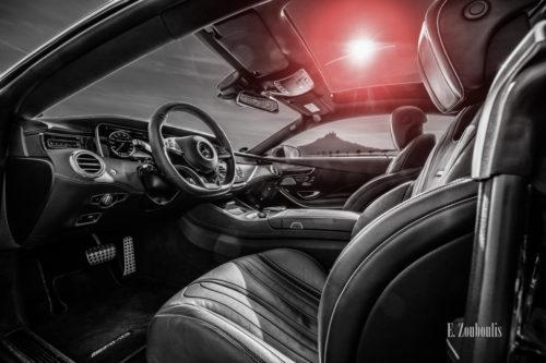 Schwarzweiß Aufnahme mit roten Elementen eines schwarzen Mercedes AMG S63 vor der Burg Hohenzollern. Blick in das Interieur der S-Klasse Durch das Fenster sieht man die Burg. Aufnahme entstanden auf Einladung von Mercedes Benz