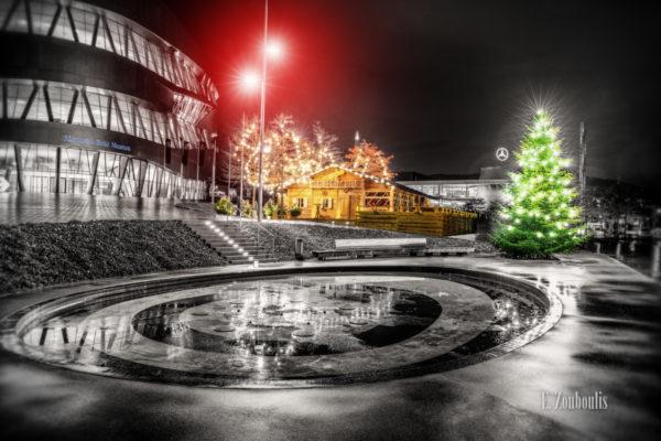 Nachtaufnahme vor der Cannstatter Hütte am Mercedes Benz Museum in Stuttgart. Schwarzweiß mit farbigen weihnachtlichen Elementen
