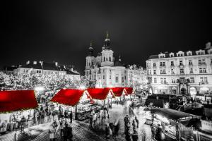Schwarzweiß Aufnahme am Weihnachtsmarkt in Prag. Im Vordergrund sind schemenhaft die Besucher zur Weihnachtszeit zu sehen. In der Mitte des Bildes rote Dächer der kleinen Verkaufsstände und im Hintergrund die die St. Nikolaus Kirche