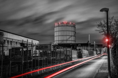Schwarzweiß Aufnahme bei Nacht am Gaskessel in Stuttgart Ost (Gaisburg). Im Vordergrund rote Lichtschweife, die den vorbeifahrenden Verkehr sichtbar machen. Der Gasturm ist hinter einer Industrieanlage mit roten Lichteffekten zu sehen. Über dem Gasturm ziehen die Wolken vorbei, die durch das Licht Stuttgart erhellt werden