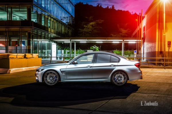 Nachtaufnahme eines BMW M3 in Stuttgart-Vogelrain. Blick seitlich auf den M3. Im Vordergrund der BMW, im Hintergrund das Gebäude des Kubus360 und der Torwiesenschule