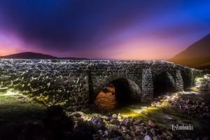 Nachtaufnahme an der Sligachan Bridge auf der Isle of Skye, Schottland. im Vordergrund die Felsen und das Wasser, das unter der Brücke hindurchfließt. In der Mitte des Bildes ist die Brücke zu sehen. Im Hintergrund die Lichter der Nacht und die Silhouetten der Berge