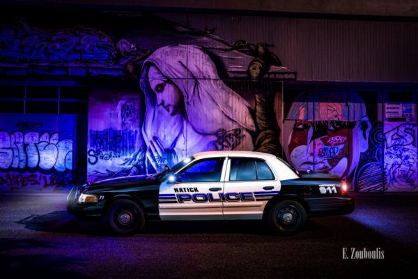 Amerikanisches Polizei Auto im Einsatz. Im Hintergrund ein Graffitti Bild eine Graffitti Wand mit einer betenden Frau von Dingo Babusch