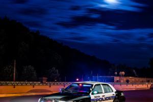 Amerikanisches Polizei Auto im Einsatz. Im Hintergrund sind vorbeiziehende Wolken zu sehen, die durch den Vollmond angeleuchtet werden
