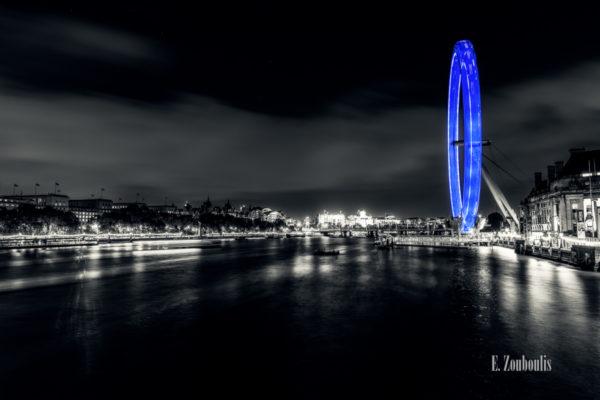 Nachtaufnahme in London. Blick auf die Themse und den blauen Lichtschweif des London Eye. Leichter Sepia-Ton mit blauem Lichteffekt