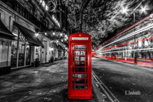 Schwarzweiß Aufnahme bei Nacht in Aldwych, London mit einer roten Telefonzelle und roten Lichtschweifen, die den vorbeifahrenden Verkehr zeigen