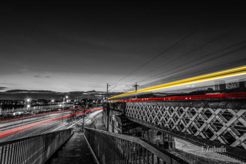 Blick hinunter auf die Pointhouse Road in Glasgow. Links ist der River Clyde zu sehen und rote Lichtschweife des vorbeiziehenden Verkehrs. Auf der rechten Seite führ ein Zug über die Brücke und hinterlässt gelbe und rote Lichtschweife