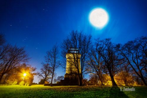 Nachtaufnahme am Bismarckturm in Stuttgart-West bei Vollmond. Im Vordergrund das Gras und gefallene Blätter. im Hintergrund der Bismarckturm, der vom Mond angeleuchtet wird