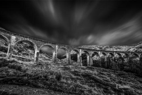 """Schwarzweiß-Aufnahme mit einer Langzeitbelichtung, die die Wolken in Ihrer Bewegung sichtbar macht. In der Mitte des Bildes befindet sich das Glenfinnan Viadukt welches als """"Harry Potter Bridge"""" aus den Filmen bekannt wurde"""