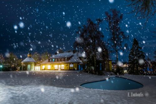 Nachtaufnahme an der Villa Schwalbenhof in Gärtringen. Im Vordergrund Schnee und der eingefrorene Teich. In der Mitte des Bildes die Villa bei einer Veranstaltung