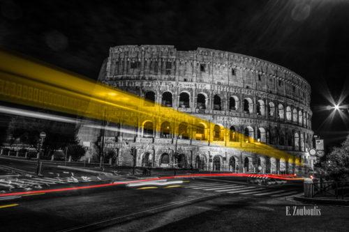 Schwarzweiß Aufnahme bei Nacht vor dem Kolosseum in Rom mit gelben und roten Lichtschweifen, die den vorbeifahrenden Verkehr sichtbar machen