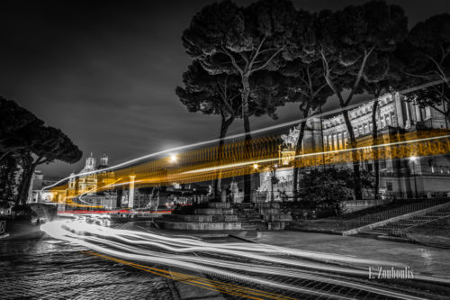 Schwarzweiß-Aufnahme am Vittoriano in Rom mit gelben und roten Lichtschweifen, die die Adern der Stadt sichtbar machen