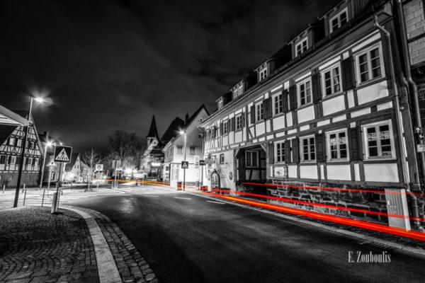 Schwarzweiß Aufnahme nachts in Gerlingen, Stuttgart mit roten Lichtschweifen, die den Verkehr sichtbar machen. Blick von der Kirchstraße auf die Weilimdorfer Straße