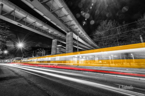 Schwarzweiß-Aufnahme am Straßenbahndepot in Stuttgart Vogelrain mit gelben und roten Lichtschweifen des vorbeifahrenden Verkehrs und der Straßenbahn