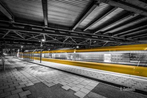 Schwarzweiß-Aufnahme am Nordbahnhof Stuttgart. Die vorbeifahrende Stadtbahn hinterlässt einen gelben Lichtschweif