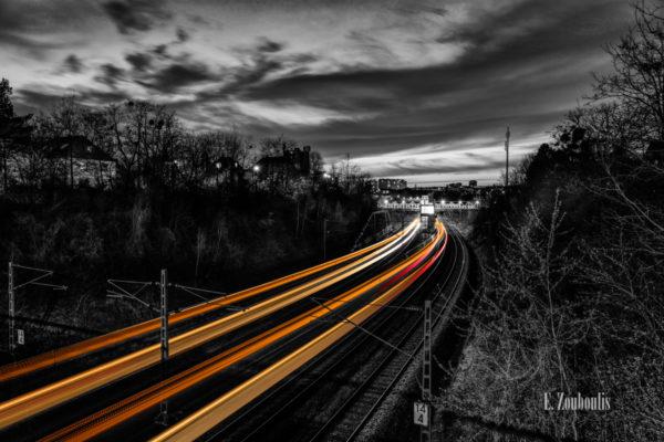 Schwarzweiß-Aufnahme bei Nacht in Österfeld, Vaihingen, Stuttgart. Rote und gelbe Lichtschweife machen den Zugverkehr zwischen den Bäumen sichtbar