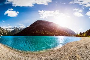 360° Panorama am Plansee, Tirol, Österreich. Im Vordergrund der Plansee, im Hintergrund die Berge, deren Spitzen noch mit Eis bedeckt sind