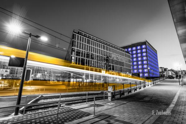 Schwarzweiß-Aufnahme an der Stadtbibliothek Stuttgart. Im Vordergrund zieht ein gelber Lichtschweif einer Stadtbahn am Betrachter in Richtung Stadtbibliothek vorbei, welche in der schönen blauen Nachtbeleuchtung zu sehen ist
