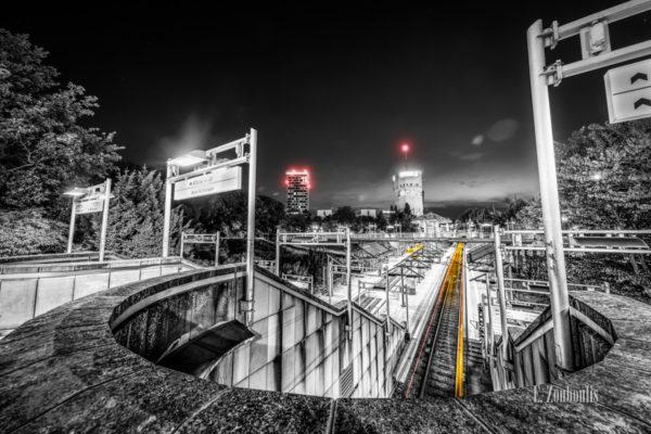 Schwarzweiß-Aufnahme am Pragsattel in Stuttgart. Blick auf einem im Vordergrund aus dem Tunnel kommenden gelben Lichtschweif einer Straßenbahn. Im Hintergrund befindet sich der Hochbunker und links davon das Hochhaus 'Skyline Stuttgart'