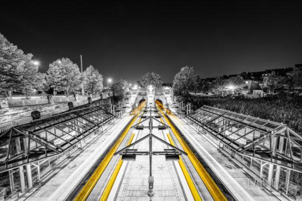 Schwarzweiß-Aufnahme am Pragsattel in Stuttgart. Die gelben Lichtschweife machen die ein- und die ausfahrenden Stadtbahnen sichtbar.