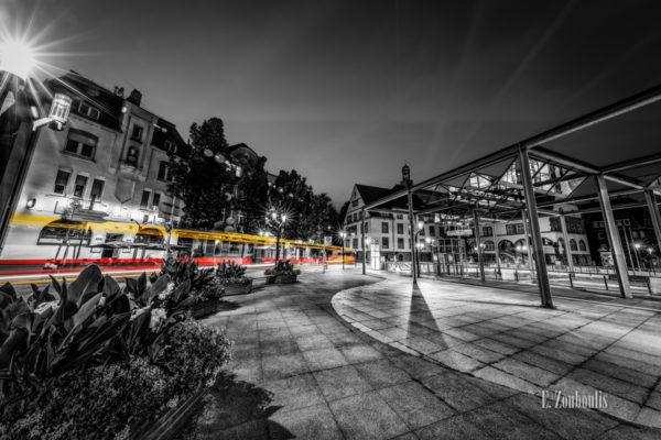 Schwarzweiß-Aufnahme am Wilhelm Geiger Platz in Stuttgart Feuerbach. Ein Bus fährt von links in die Mitte des Bildes und hinterlässt einen gelbroten Lichtschweif. Im Hintergrund ist das Bürgerbüro Feuerbach zu sehen