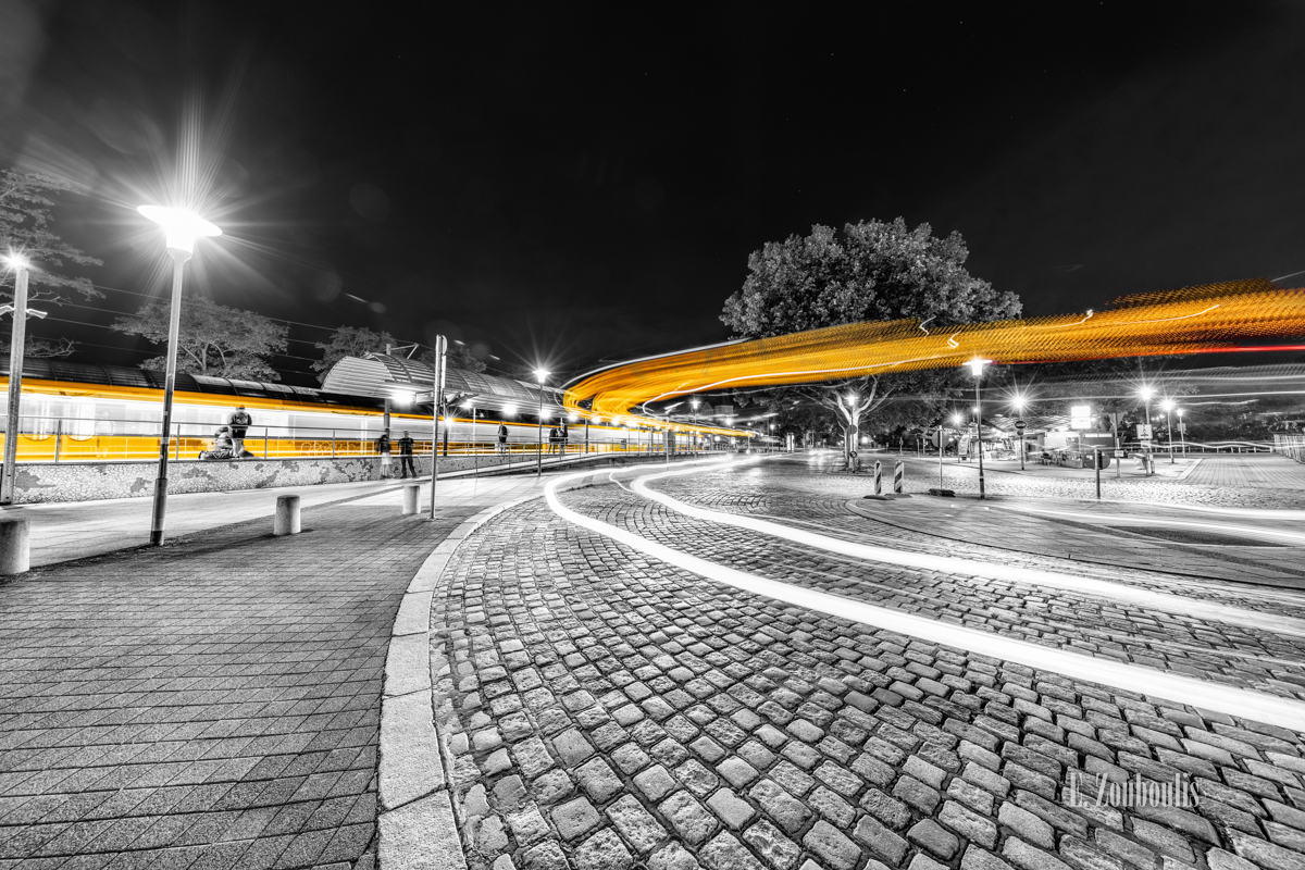 Schwarzweiß-Aufnahme am Bahnhof in Stuttgart-Feuerbach mit gelben Lichtschweifen von ein- und ausfahrenden Straßenbahnen und Bussen