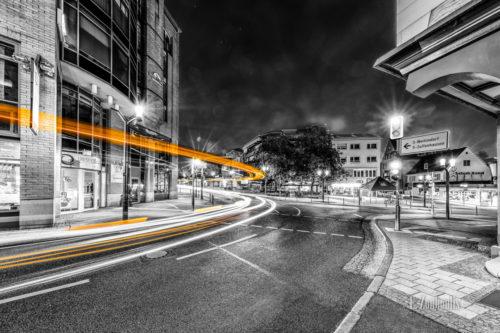 Schwarzweiß-Aufnahme bei Nacht in Stuttgart-Feuerbach. An der Stuttgarter Straße 'fliegt' ein Bus vorbei und hinterlässt einen gelben Lichtschweif