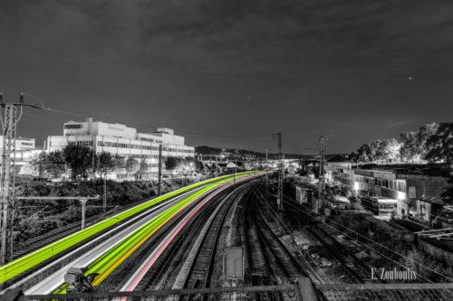 Schwarzweiß-Aufnahme in Stuttgart-Feuerbach mit grünen und roten Lichtschweifen, die die vorbeifahrenden Züge in der Nacht sichtbar machen