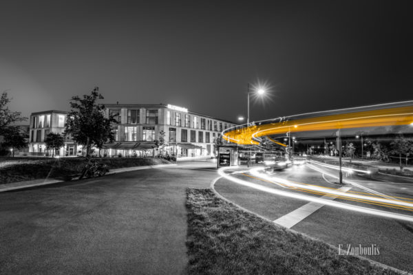 Schwarzweiß-Aufnahme auf der Killesberghöhe in Stuttgart. Im Hintergrund ist das Einkaufszentrum und der Killesbergpark zu sehen und im Vordergrund hinterlässt der vorbeifahrende Bus einen gelben Lichtschweif